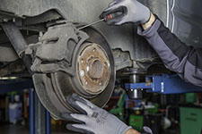 image of a man servicing a cars breaks